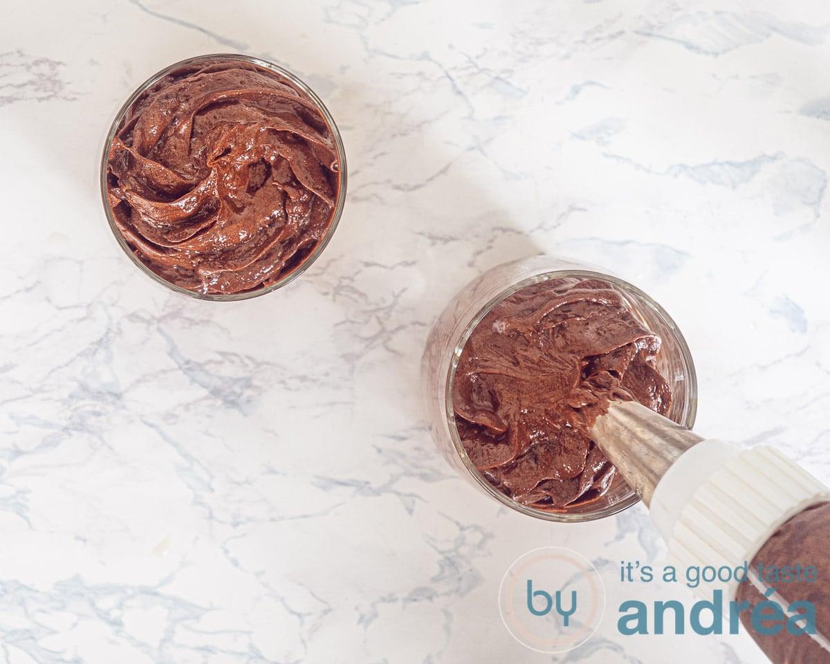 Een spuitzak die chocolade mousse in een glas spuit
