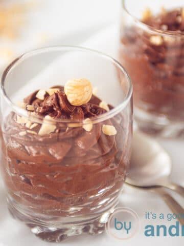 Twee glaasjes met chocolade mousse met hazelnoten topping