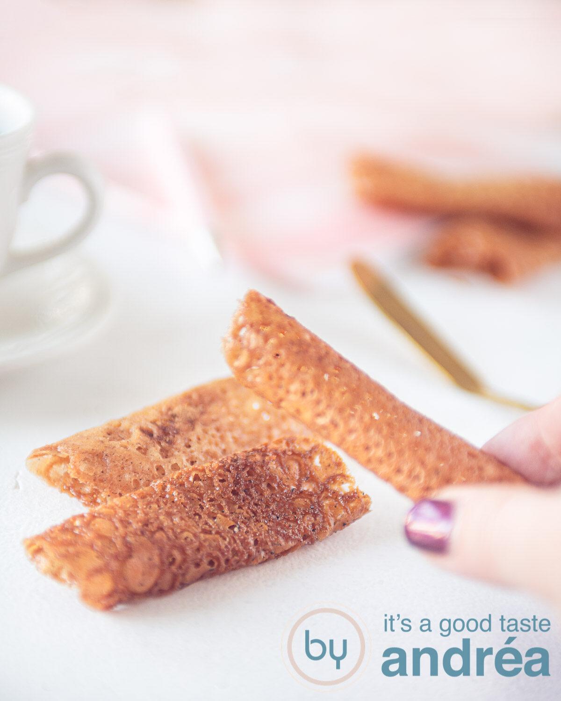 een hand die honing tuiles van een stapeltje afpakt. Op de achtergrond een witkopje en een roze doek