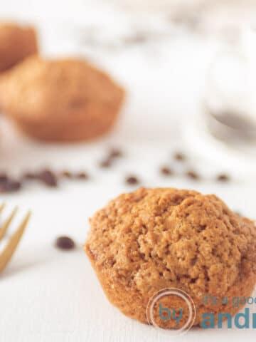vierkante foto met een koffie muffin op de voorgrond en een stapeltje muffins op de achtergrond. Wat koffiebonen verspreidt