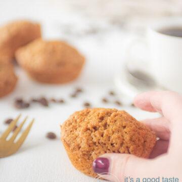 Een hand die een muffin van de tafel pakt. Een kopje koffie en extra muffins in de achtergrond.