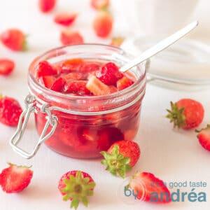 vierkante foto, een pot met aardbeiensaus omringt door aardbeien wat bakjes in de achtergrond