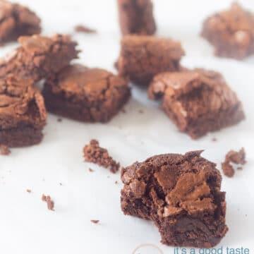 Smeuïge brownies met chocola verdeeld over een tafel. Bij de voorste is er een hapje uitgenomen