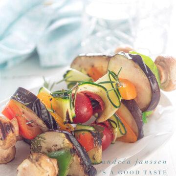 drie vegan kebabs gegrild, op een witte plaat. Een blauwe handdoek achterin