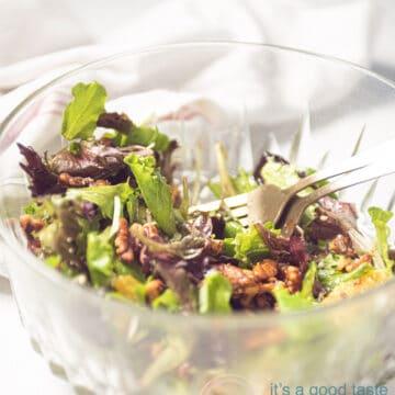een glazen schaal met twee gouden vorken en een sinaasappel salade
