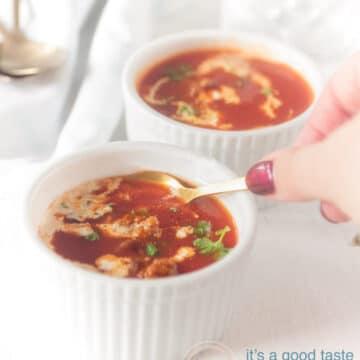 Twee witte kopjes gevuld met tomatensoep, gehaktballetjes en een drupje room. Een hand die een lepel vasthoud die een hapje neemt.