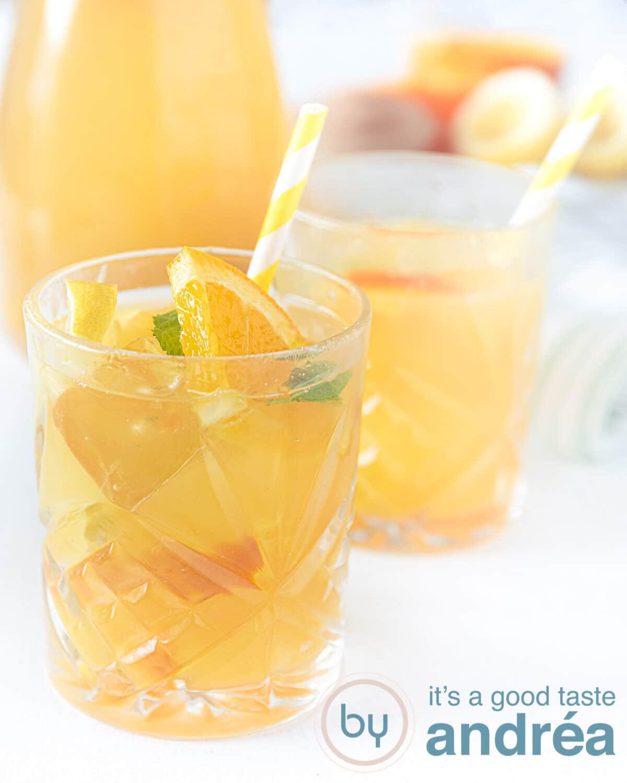 Twee glazen sinaasappel ijsthee een karaf in de achtergrond