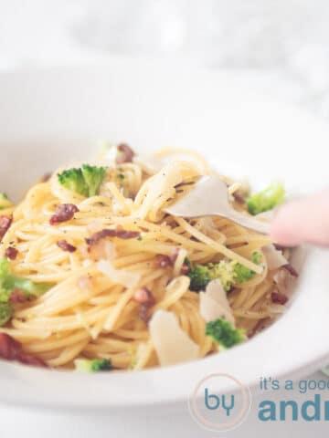 Een vierkante foto met een bord spaghetti, een hand die er wat uitpakt en brocolli, spekjes en Parmezaanse kaas