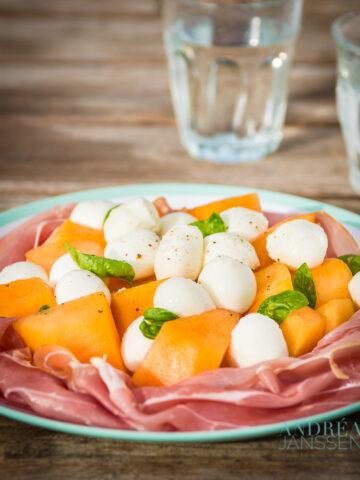 salade van meloen, ham en mozzarella op een bord