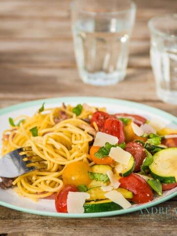 Spaghetti met roerbak courgette op bord met glazen water