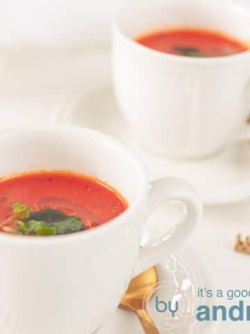 een vierkante foto met twee kopjes gevuld met tomatensoep en gegarneerd met kruiden
