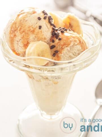 Een vierkante foto met een glas gevuld met ijs van bananen chocola en saus
