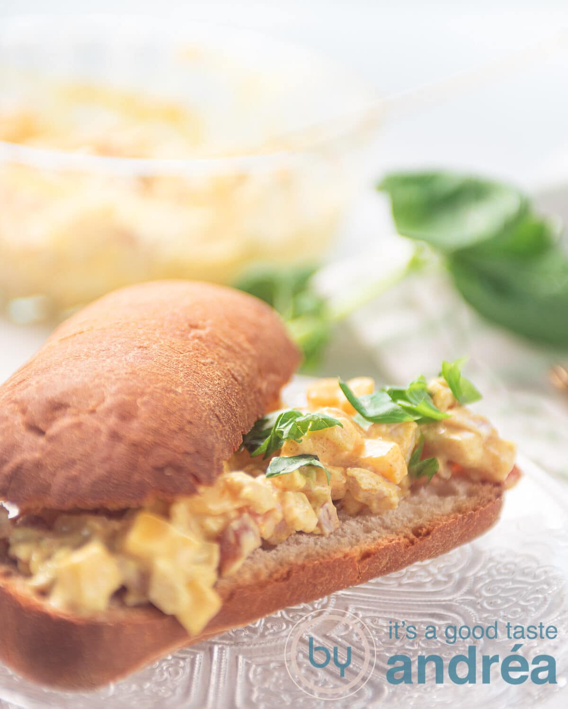 Een glazen bord met een opengesneden broodje met gerookte kip mango salade. Een schaal met meer salade op de achtergrond