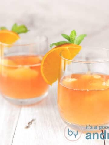 Op een witte ondergrond staan twee glazen met sinaasappel oranje cocktail