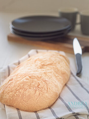 Zelfgebakken ciabatta op een keukendoek met mes en eetgerei