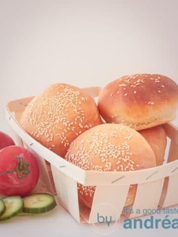 4 hamburgerbroodjes in een houten schaaltjes met tomaat en komkommer