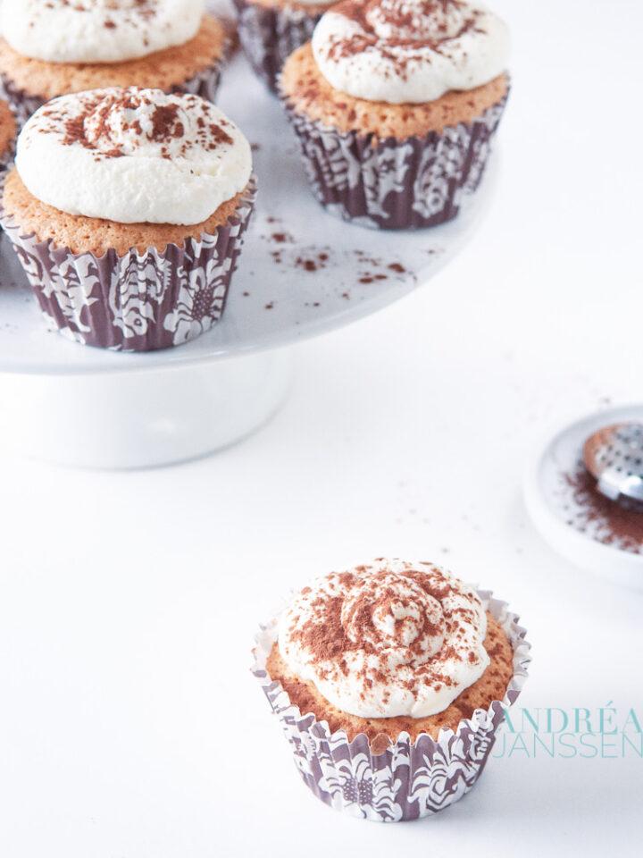 Tiramisu cupcakes op cakestandaard en ervoor met cacao