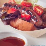 Braadworst op een broodje met garnering van groenten en curry