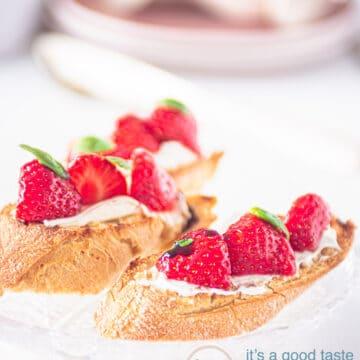 twee bruschette met roomkaas, daarop aardbeien en creme balsamico. Op de achtergrond servies