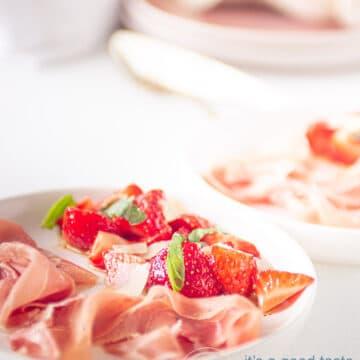 Op een wit bord aardbeien gemarineerd in creme balsamico met ham, op de achtergrond servies