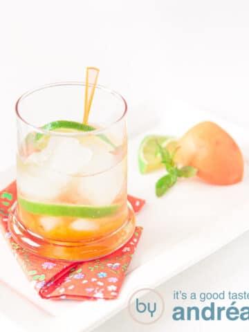 een glas met abrikozen caipirinha met garnering abrikozen en limoen