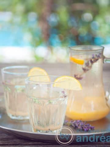 Twee glazen met lavendel limonade gegarneerd met citroen en een kan met limonade in een zomerse achtergrond