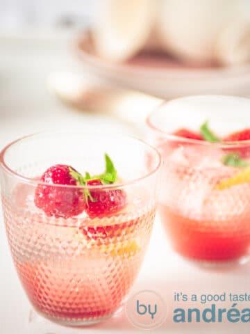 Twee glazen met limonade met aardbeien en citroen als garnering