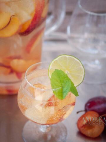Een glas met Sangria bianco en fruit, gegarneerd met munt en citroen. Een kan en glazen op de achtergrond