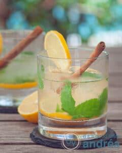 Twee glazen Caipirinha thee cocktail met munt, kaneel en citroen tegen een zomerse achtergrond