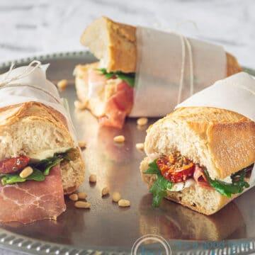 3 heerlijke broodjes met ham, rucola, mozzarella en zongedroogde tomaatjes in papier gerold op een zilveren plaat