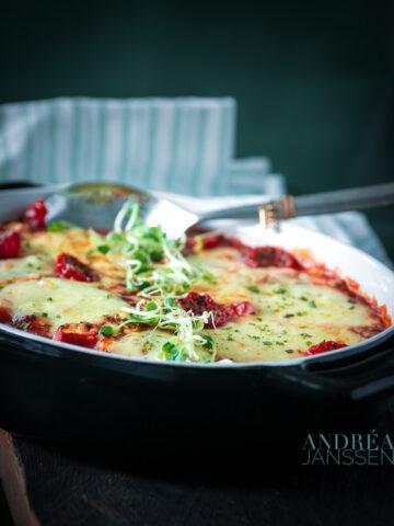 een zwarte ovenschaal met schnitzel en veel groenten. Een groen wit gestreepte theedoek