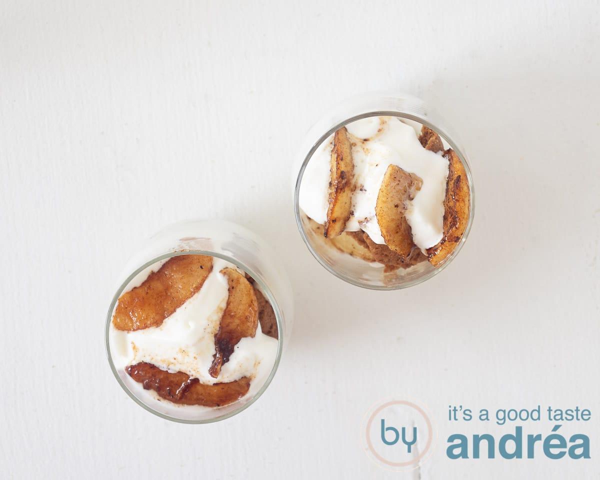 Twee glaasjes gevuld met koek, slagroom en gebakken appels