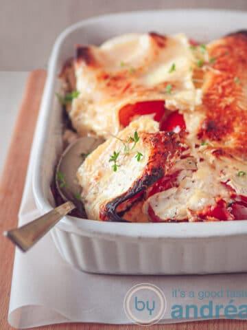 Een schaal met vegetarische lasagne waaruit een lepel wordt geschept