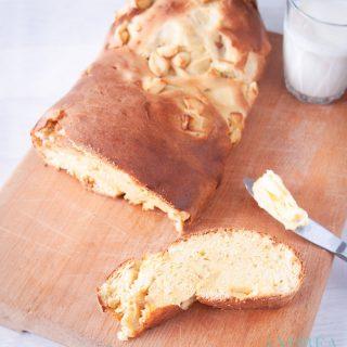 Een appelbrood op een snijplank, gesneden met wat boter