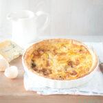 Een tafel met een appel gorgonzola quiche en wat ingrediënten