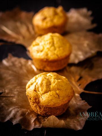 3 mais muffins op een rij op gouden blaadjes