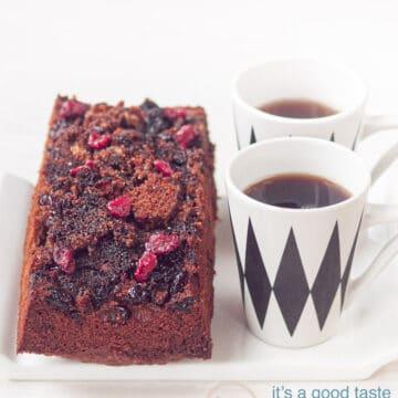 Op een wit schaaltje ligt een cake met cranberry topping en twee kopjes met koffie