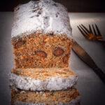 Wortelcake met pepernoten op een betonnen ondergrond. Een plakje is afgesneden