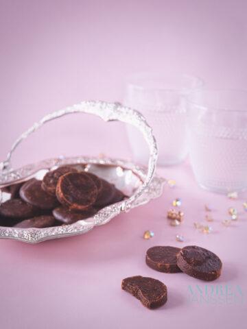 chocolade borstplaat in een schaaltje en enkele op de voorgrond. Een roze achtergrond