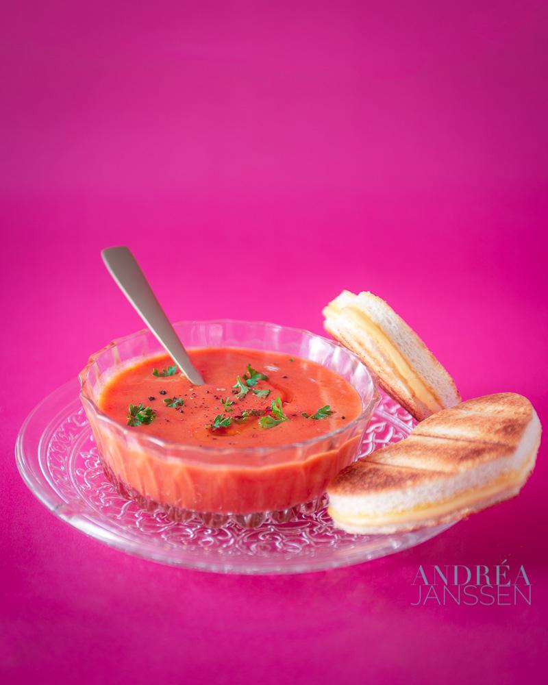 een glazen kom met tomatensoep, hartjes tosti op een roze achtergrond