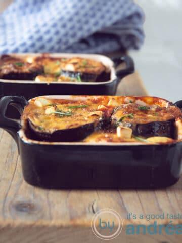 Twee een persoons Griekse moussaka ovenschotel bakjes en een blauwe theedoek