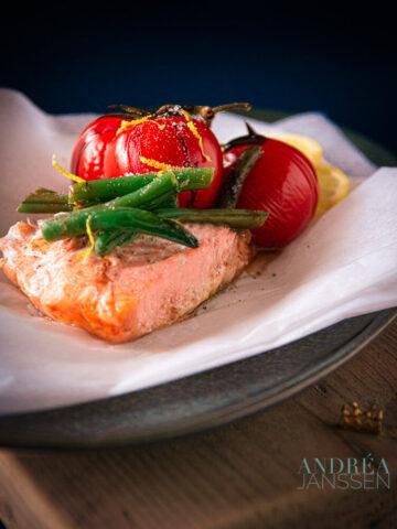 een opengevouwen zalmpakketje uit de oven met tomaten en groenten
