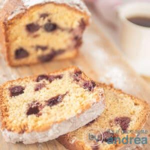 Een vierkante foto van een cake met blauwe bessen en een kopje koffie