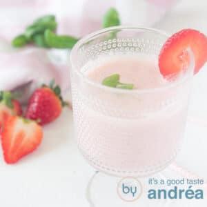 een vierkante foto met een glas met aardbeiensmoothie. Gegarneerd met aardbeien en basilicum