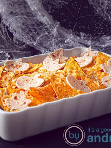 Een witte ovenschotel in Halloween stijl gevuld met kip, boontjes, tomaat en afgedekt met nacho chips en tortilla en kaas