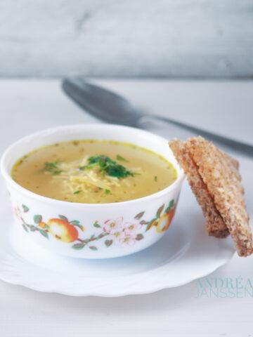 een kommetje met vermicelli soep en een sneetje brood