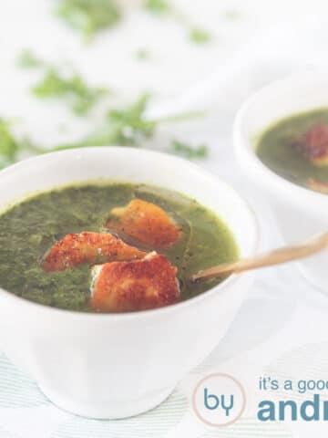 vierkante foto met twee witte kommen met soep van spinazie, boerenkool en paksoi. Met een topping van Halloumi