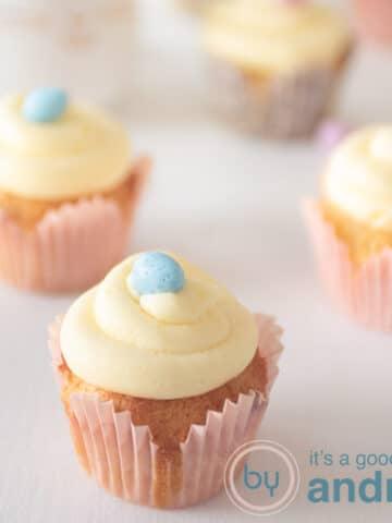 Vierkante foto met vier cupcakes met een paasei, vanille cupcake en boter crème topping