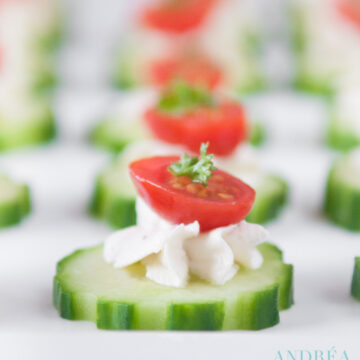 een schaal met komkommers, een roomkaas topping en een halve cherry tomaat als topping.