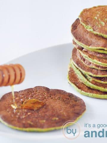 Vierkante foto, links een spinaziepannenkoek met een houten lepel met honing. Rechts een stapel spinaziepannenkoeken